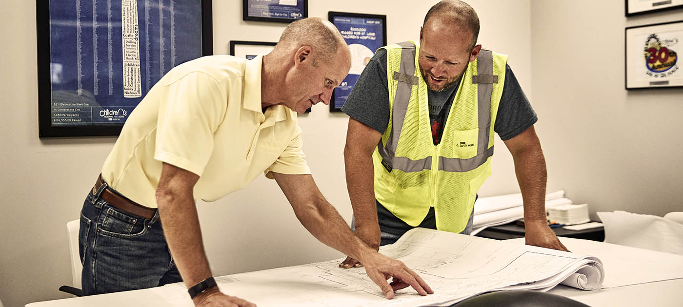 Two men consulting blueprints