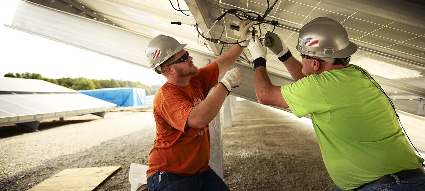 Two construction workers wiring a solar panel