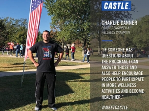 charlie danner stands in front of an American flag in a park full of people